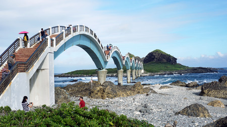 Taitung, Taiwan - Dec. 5, 2018 - Sanxiantai Dragon Bridge with tourist walking to Sanxiantai Island, Sanxiantai means platform of the three immortals.