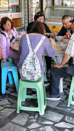 Hualien City, Taiwan - Dec.2, 2018 - A typical busy restaurant in Taiwan with plastic chairs.