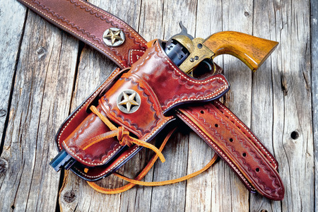 Antique western cowboy pistol in leather holster. Stock Photo