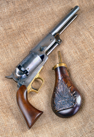 Antique Cowboy percussion pistol and  copper gunpowder flask. Stock Photo