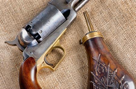 Pistolet à percussion Cowboy antique et flacon de poudre à canon en cuivre. Banque d'images