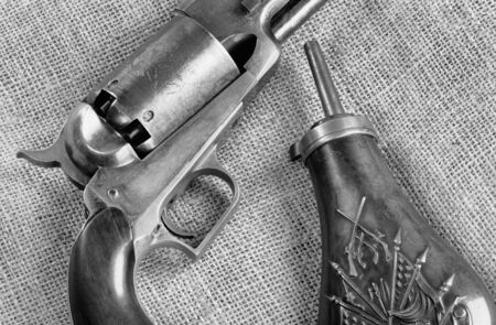 Antique Cowboy percussion pistol and copper gunpowder flask in black and white. Stock Photo