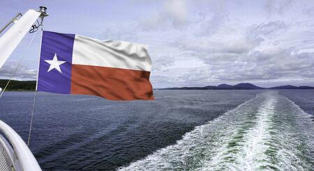 Texas flag flying high against the blue water waves. Stock Photo
