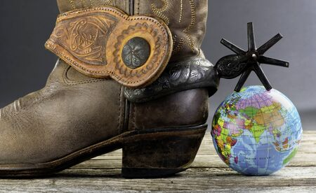 World cowboy with Mexican spurs and small globe. Reklamní fotografie