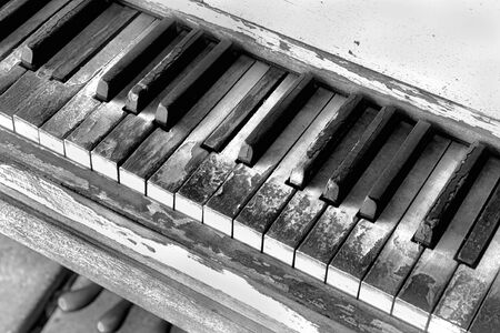 Old broken piano keys in black and white.