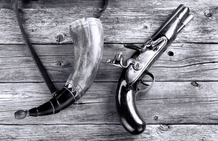 Antique English flintlock pistol and gunpowder horn made around 1800 in black and white. Imagens