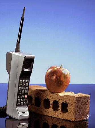 Old cell phone called the brick phone with a red apple made in the early 1980s.