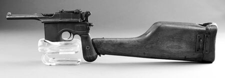 Antique German broomhandle pistol made around 1926 with attached wooden shoulder stock in black and white. Imagens