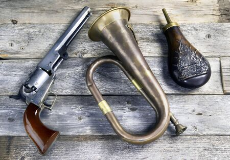 Antique cowboy pistol, brass bugel and gunpowder flask. These would be items a civil war soildier would carry.