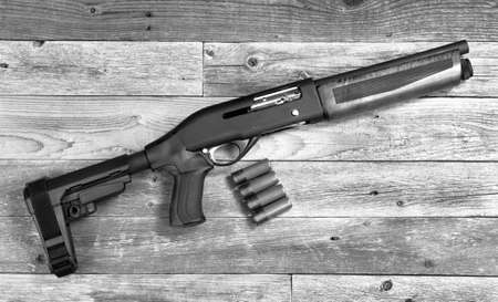 Home security 12 gauge short barrel semi- auto firearm/ shotgun in black and white.