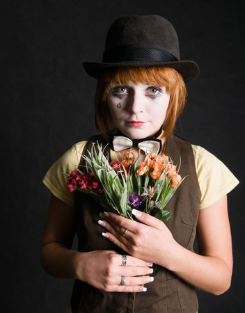 Sad clown with bouquet photo