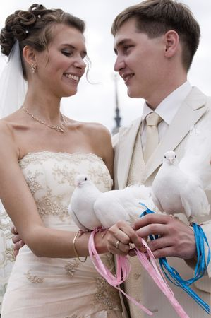 Young newlyweds holding two white doves on their hands. White doves are the symbol of love and togetherness.  photo