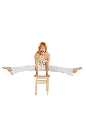 Red haired girl performing fitness exercises on white background