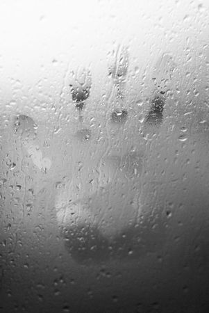 Water drops on glass window with a human hand shape imprinted