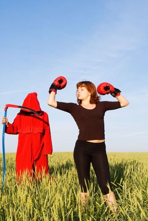 boasting: Healthy sporty girl and spooky figure in red hood with a scythe Stock Photo