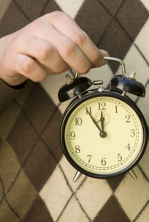 Hand holding alarm-clock with 5 min before noon on it. Stock Photo - 5711984