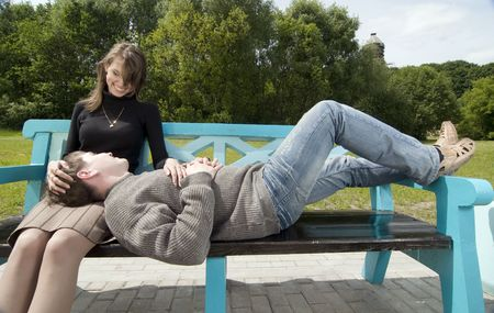 laps: Happy young couple on a blue bench Stock Photo