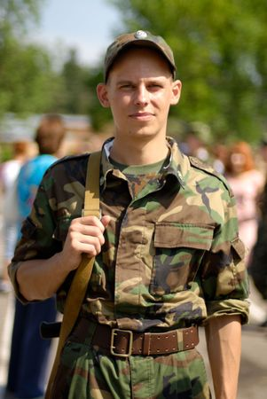 armed services: Young soldier poses with some civilians in the blurred out-of-focus background