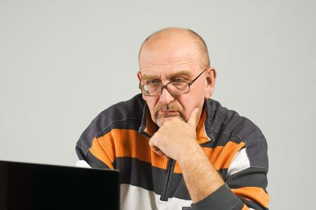 Mature man sitting at the table with laptop photo