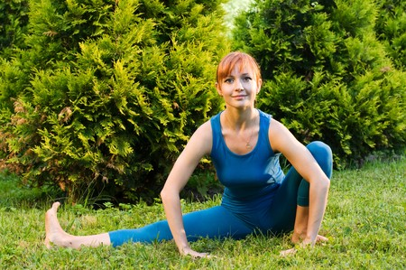 Beautiful red woman doing fitness or yoga exercises outdoors in a green park photo