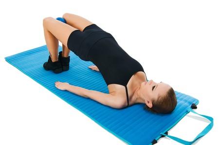 Mooi passen rode meisje beoefenen van pilates of callanetics met bal en blauwe yoga mat  Stockfoto