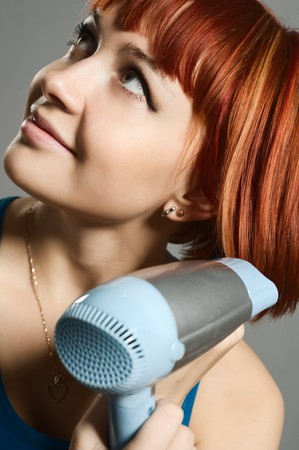 Woman with hairdryer and a hairbrush taking care of her red hair photo