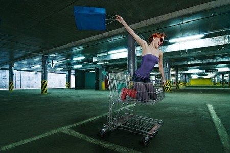 Red girl riding shopping cart at the mall undergroundparking photo