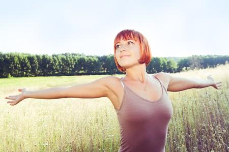 Gelukkig rode meisje met uitgestrekte handen buiten in het veld  Stockfoto