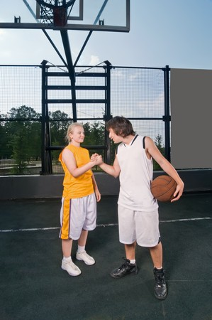 Two teenagers exchanging friendly handshake after streetball match Stock Photo