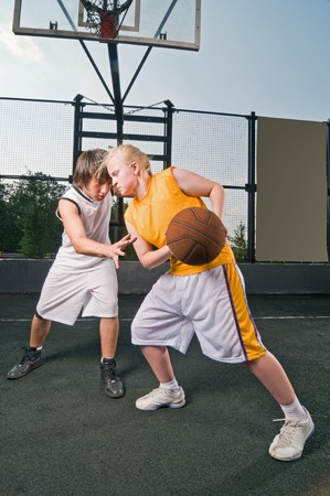 Teenage boy and girl playing basketball at the street playground  photo