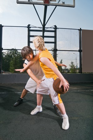 Two teenagers playing one-on-one at the streetball playground photo
