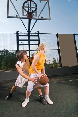 Two teenagers playing streetball with boy defending against girl photo