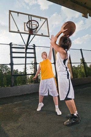 outdoor basketball court: Two teenagers playing basketball at the street playground