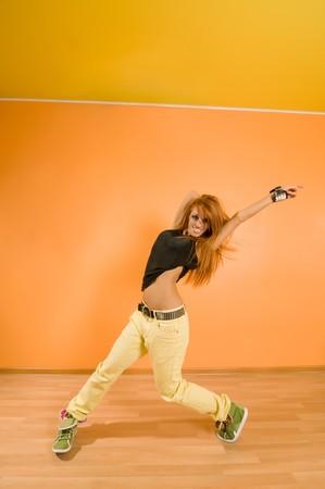 Red hair girl dancing hip-hop over vivid background