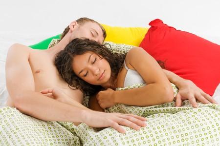 Jonge mannen en zijn zaak in bed liggen en bij elkaar te houden