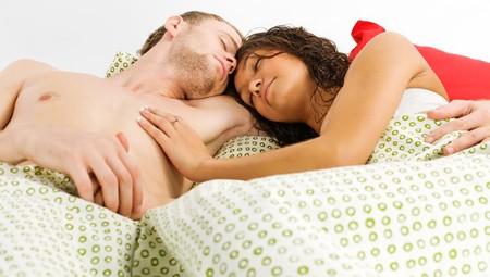 Junge Männer und seine Affäre im Bett liegend und zusammenhalten  Lizenzfreie Bilder