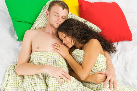 Happy young couple relaxing in bed in surrounding of colorful pillows photo