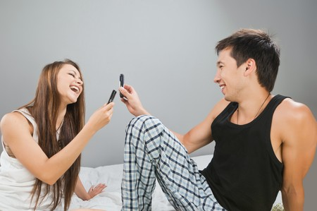 Happy young couple with cellulars in bed photo