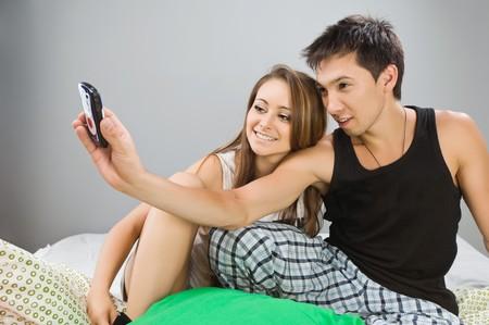 Gelukkige jonge paar in bed met mobiele
