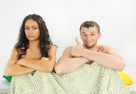 Young couple having happy leisure time in bed photo