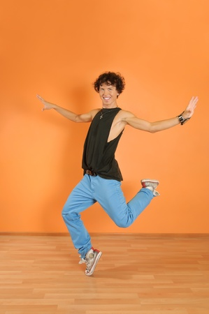 Young man perform break dancing moves on vivid background photo