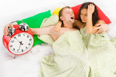 Young couple annoyed by big alarm clock at monday morning Stock Photo