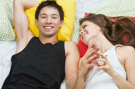 Happy young couple in bed enjoying each other photo