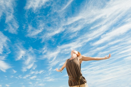 Beautiful young dancer performing yoga-dance outdoors with blue sky and clouds in the background photo