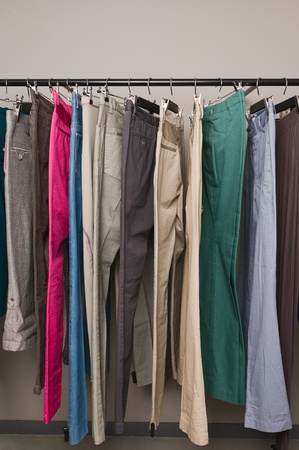 clotheshanger: Many jeans on hangers at the store for sale
