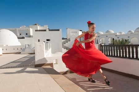 Aantrekkelijke flamencodanseres dragen van traditionele rode jurk met bloem in het haar Stockfoto