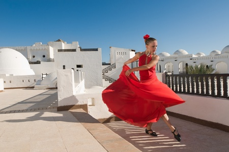 spanish dancer: Attractive flamenco dancer wearing traditional red dress with flower in her hair