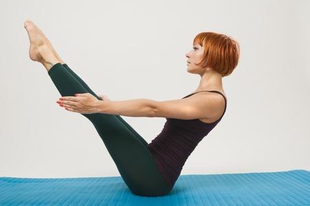 Red woman practicing fitness yoga Standard-Bild