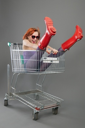 Red girl riding on a shopping cart photo
