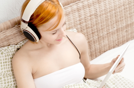 Red woman in bed listening to the music Stock Photo